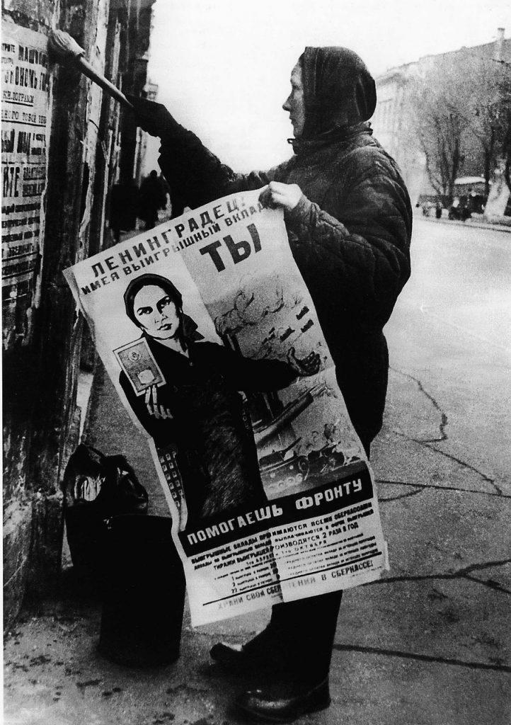 1943. Женщина расклеивает агитационные плакаты в блокадном Ленинграде