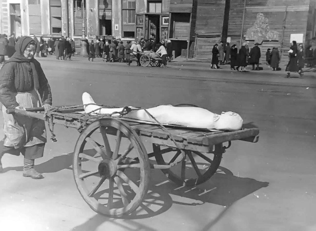 Жительница блокадного Ленинграда везет тело умершего на ручной тележке