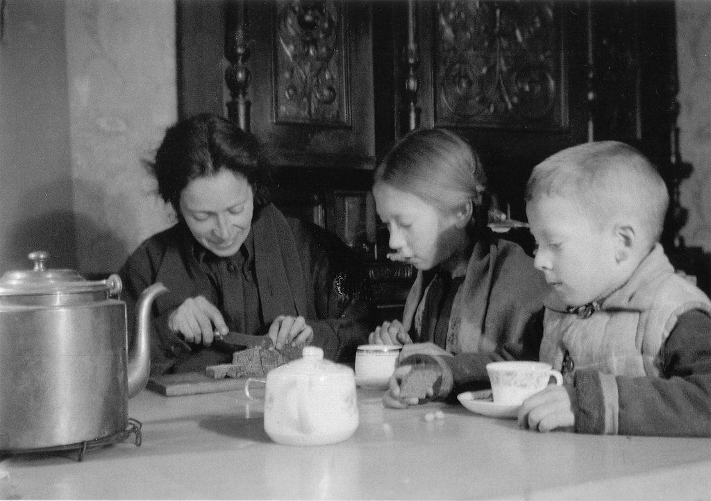 Учительница музыки Нина Михайловна Никитина и ее дети Миша и Наташа делят блокадный паек. Февраль 1942 г.