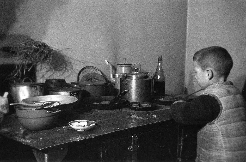 Школьник Миша Никитин у кухонной плиты в блокадном Ленинграде. Январь 1942 г.